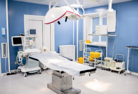 Operation table with large lamps above inside contemporary surgery room